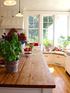 What a wonderful kitchen space! Wood countertops, large windows with bench seating and comfy throw pillows.