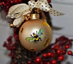 This is a beautiful ornament, perfect for anyone who likes or keeps bees! This elegant hand painted golden frosted bee glass ornament features a bee with a Swarovski topaz rhinestone and painted stain glass honeycombs which encircle the 2.64 inch ornament. A ribbon is attached on