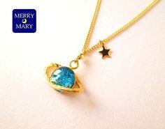 金色の輪っかをまとった土星のネックレスです。<サイズ>ミール皿:8mmチェーン:40cm+アジャスター 5cm<素材>レジン製ネックレスチェーン、ヒキワ(カニ...|ハンドメイド、手作り、手仕事品の通販・販売・購入ならCreema。