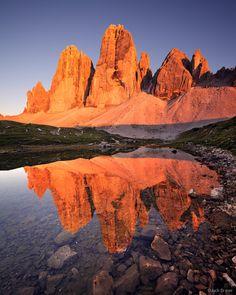 Brilliant enrosadira sunset light on Tre Cime di Lavaredo / Drei Zinnen (2998m) reflected in a small lake. Photo © copyright by Jack Brauer....