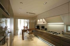 Luxus hangulatú konyha magasfényű felületekkel, fa étkezőpulttal