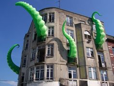 An artist calling himself 'FilthyLuker' installed inflatable octopus tentacles in the windows of an unnamed building in June of 2009, making it appear as if the building is being devoured by a bright green kraken that somehow emerged from the sea and got stuck inside.