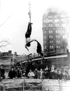 Master illusionist and escape-artist, Harry Houdini hangs above the crowd after undoing a straight jacket while hung upside down. Houdini was a superstar in his day. Art Of Manliness, Straight Jacket, Urban Life, The Conjuring, Back In The Day, Stunts, The Magicians, Illusions, The Past