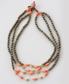 Glimmering accent pieces combine with rose and stone colored paper beads in this sparkling addition to our collection.