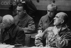 SS Colonel Joseph Vogt, left, and Oswald Pohl, chief economic officer of the SS and director of concentration camp work programs in Germany during World War II, listen as an indictment is served at their trial. Nuremburg, 1945.
