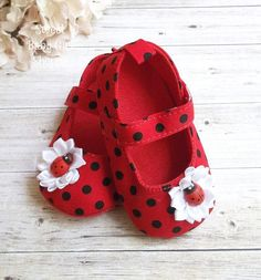 Heres a cute pair of Ladybug shoes, perfect for her Ladybug First Birthday Outfit! They are red with black polka dots. Weve attached white satin flowers and adorable wooden ladybug buttons. They have velcro straps to keep them secure. What a great addition to her Ladybug outfit or