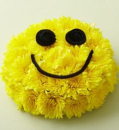 Smile Bouquet®- Vibrant yellow cushion poms designed in floral foam and tray to resemble a birthday cake $39.99