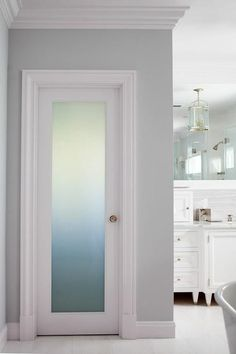Fantastic bathroom boasts a frosted glass water closet door accented with a brass door knob.