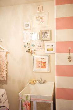 Love the stripes and the knobs as well as the cute photo wall in the laundry room!