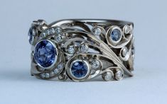 Blue sapphires and diamonds sparkle amid palladium white gold curls and whorls in this hand-crafted ring by Dmitriy Pavlov, represented at Studio Jewelers - Madison, WI Bridal Jewelry, Gemstone Jewelry, Saphire Ring, Hand Piercing, Blue Sapphire, Handcrafted Jewelry, Jewelry Crafts, Cuff Bracelets, Curls
