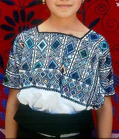 A Maya woman from Zinacantan Chiapas, wears an embroidered huipil from San Andres Larrainzar. Many women from Zinacantan buy and wear huipil...