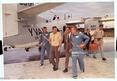 Cape Kennedy, Florida. Gemini 7 astronauts Frank Borman (far left) and James Lovell (far right), are greeted upon their arrival at Cape Kennedy by fellow Astronauts Alan Shephard (wearing suit) and Donald Slayton (yellow shirt), December 19th. Borman and Lovell were flown to the cape from the carrier wasp after completion of their historic two-week space mission.