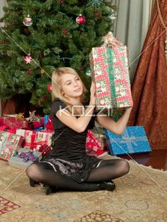 little girl opening gifts - Child holding gift sitting beside a Christmas tree. Model: Shania Chapman - Agent is Breann at MMG. breann@nymmg.com