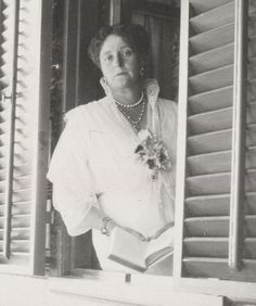 A tired-looking Empress Alexandra stands in a window in this photo.