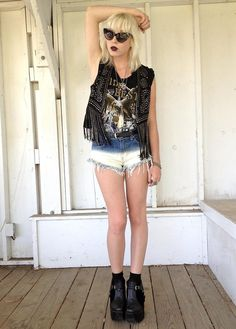 Half-bleached shorts and a fringed vest with a graphic t-shirt make dark, gothic lips rock-n-roll