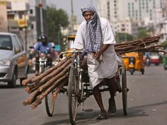 A laborer covers himself with a cloth to protect from the sun as he pulls a rickshaw carrying wooden logs on a hot summer afternoon in Hyderabad, India, Friday, May 20, 2016.India sweltered to a scorching 123.8 degrees Thursday, setting a new all-ti USA TODAY