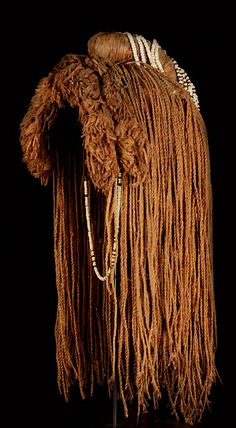 "Central Africa, Angola, Mubukush People  This quality example is made of strands of woven bush fiber resembling human hair, each of which is attached to a piece of leather hide on the interior.  Two rows of clustered fiber on the front, make for lavish and full bangs.  The central crest is adorned with beaded fringe of white, black, red and blue which terminates into a long elegant pigtail!  There is no synthetic materials used whatsoever.  . ..  Dimensions:  Length 21"",  width 11"""