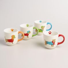 Celebrate your furry friends with our quirky dog mugs, featuring four pooches in winter attire, colored handles, and a paw print inside. This set makes a thoughtful holiday gift for your favorite animal lover.