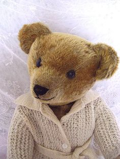 This outstanding early American teddy bear is honey colored mohair and has boot button eyes and floss nose and mouth. He is jointed at the neck, arms