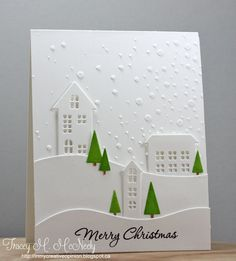 handmade Christmas card by tracey ... winter scene make with die cuts and stenciling ... mostly white on white ... tiny bright green triangle trees add bits of color ... stencil paste dots ... die cut houses and snowdrift lines ... stupendous look!