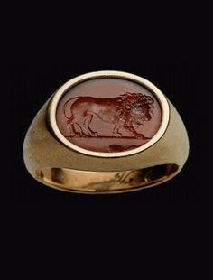 Ringstone with lion.  Roman -  Imperial Period,  1st or 2nd century A.D. | Carnelian intaglio ringstone in modern gold setting, lion walking to right on a ground-line. Stone chipped on edge below groundline. Gold band inscribed.