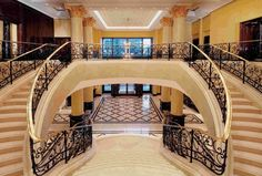 Open foyer with straight staircase descending from small upper ...