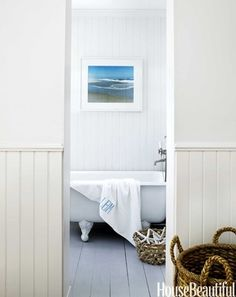 beautiful white bath tub lovely white floorboards & clad walls pops of blue & rustic wicker baskets