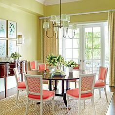 A Splash of Bold Color | This room features a lettuce green shade on the walls and kicks it up a notch with bright coral upholstered dining chairs. | SouthernLiving.com