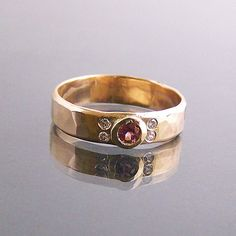 This is a very classic design. The hammer finish on this 4.5mm wide 14k yellow gold ring gives it a nice texture and lets the light dance off the band. I set a 3mm Rhodolite Garnet in the center and surrounded it by 4 1.5mm Diamonds (E color, VS qual Code: 10PERCENT for 10% off at MedallionTradingCompany.com