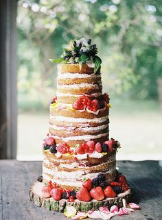 Beautiful Three Tier Naked Wedding Cake Decorated With Summer Fruits and Topped With Flowers