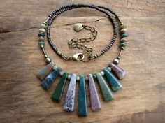 I created this unique tribal style statement necklace using a series of graduated sanctuary India agate sticks as the focus. The primary colors are pine and forest green, but it also features shades of pinkish gray, pinkish tan, and caramel. The stone sticks and the stones flanking either side are agate, while the small spacer stones are fancy jasper. The metallic accents include iron pyrite spheres and antiqued brass tubes. The remainder of the piece is comprised of Japanese seed beads. I…