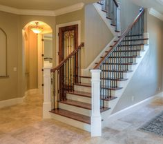 The most prominent feature of the open foyer is the staircase. Outfitted with oak treads, painted risers and newel posts, and iron balusters, it leads to secondary bedrooms and an oversized loft. A large wall niche is perfect for showcasing prized artwork. A wine room with a decorative iron door is behind the staircase. To the left of the wine room is a foyer leading to the master bedroom. Floors are travertine tile.