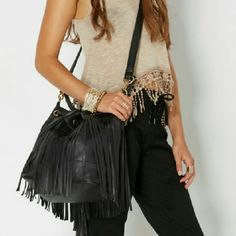 [NEW]  Fringe Bucket Bag Condition: New Flaws: None Color: Black Measures Approx: 11.5 in. high x 10 in. wide Materials: Faux Leather Drawstring closure; adjustable shoulder straps Interior zip and compartments Bags Crossbody Bags
