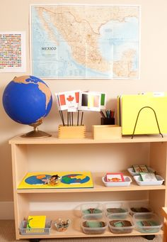Culture and Science shelves. The first shelf contains Sandpaper Globe, a flag stand, and Geography Folders for each continent. Botany and Zoology nomenclature cards and a Puzzle Map of the World are on the second shelf. Handmade Land and Water Forms are set out on the bottom shelf.