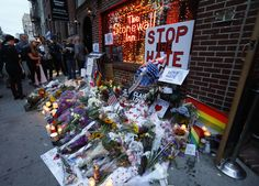 People gather to look at a makeshift memorial for victims of the Orlando nightclub shootings in front of the historic Stonewall Inn, a gay bar in the West Village, on June 13, in New York.