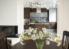 Studio Mebica STÓŁ W KUCHNI Otwarta kuchnia z widokiem na salon. Zastosowanie brązowych mebli w kontraście z jasnymi ścianami i dodatkami.