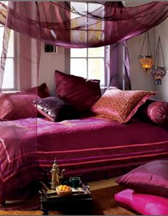 Bohemian inspired bedroom is decorated in dramatic shades of Magenta