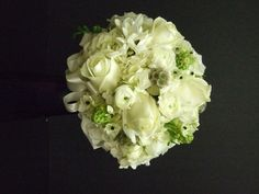This bride's bouquet of white roses and hydrangea get a touch of color from star of Bethlehem - both as the white flower with the black center as well as the green unopened flower, Scabiosa pods also add another textural element.  See more wedding bouquets, centerpieces, and more at www.jeffmartinsweddings.com