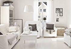 Vasemmalla oleva vanha ranskalainen kaappi kätkee sisäänsä muun muassa tekstiileitä. Nojatuolit, sohva ja rahi ovat Ikeasta. Vanhan sohvapöydän jalat on katkaistu lyhyiksi, pöytä on hiottu ja maalattu valkoiseksi.