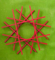 """Geometric Wood Slat Wreath  Cut six 36"""" square dowels (#27594) in half to make a dozen 18"""" pieces. Paint them red and glue together in a tic-tac-toe pattern to create a center circle."""