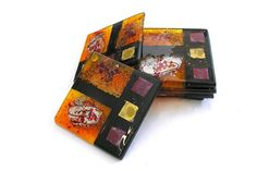 Set of 6 Amber Handmade Glass Coasters – Troy: Ilium Revealed Collection £26.00  A set of six square fused glass coasters from the deep, thought provoking Troy collection. Rich oranges, gold, silver and black merge in a contemporary design.
