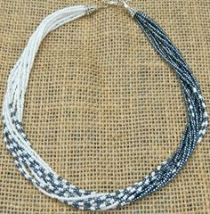 Short seed bead statement necklace multi strand gunmetal, white, feather impression.