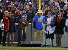 """#WorldSeries2013 #Bosox #SLCardinals James Taylor sings """"God Bless America"""" alongside Carlos Arredondo, center, and Boston Marathon bombing survivor Jeff Bauman, second from right, during the seventh inning stretch of Game 2 of baseball's World Series between the Boston Red Sox and the St. Louis Cardinals Thursday, Oct. 24, 2013, in Boston. (AP Photo/Matt Slocum)"""