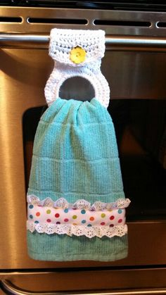 Crocheted towel holder with trim of ribbon and eyelet sewn on towel.