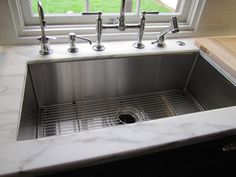 Kitchen with deep under mount stainless steel sink, Kohler polished metal faucet and fittings and marble countertop