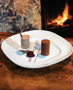 This beautifully plated chocolate dessert by the fire is getting us in the mood for winter! #AUIFineFoods #Chocolate #Dessert