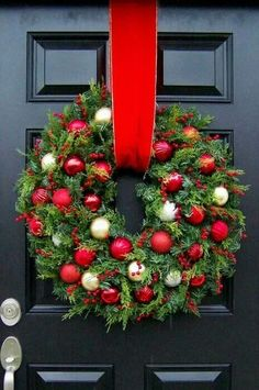Combine multiple wreaths of different sizes. Hang with wide ribbon.