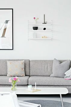 string pocket shelf above grey sofa