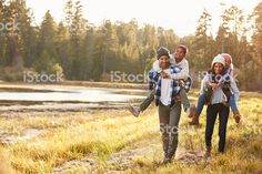 Parents Giving Children Piggyback Ride On Walk By Lake royalty-free stock photo