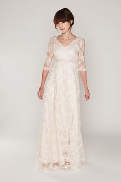 Embroidered European lace tulle overdress; assymetrical bodice with a button-up closure on the back. Delicate, transparent, 3/4 length sleeves. Underneath is a stretch silk charmeuse slip dress. Empir